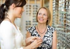 Femme avec la vendeuse sélectionnant des verres dans le magasin Images stock
