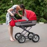 Femme avec la voiture d'enfant Photo stock