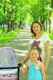 Femme avec le bébé dans la fille de voiture landau et d'aîné Photos libres de droits