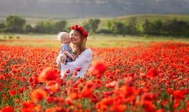 Femme avec le bébé dans un domaine des pavots rouges Photos stock