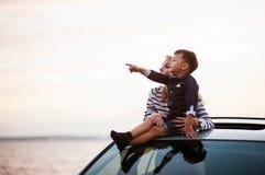 Femme avec le bébé sur le toit de voiture Images libres de droits