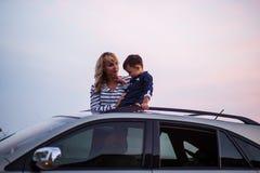 Femme avec le bébé sur le toit de voiture Photographie stock libre de droits