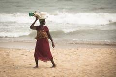 Femme avec le bébé sur une plage dans la côte de cap, Ghana Image stock