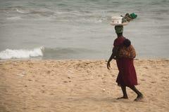 Femme avec le bébé sur une plage dans la côte de cap, Ghana Photo libre de droits
