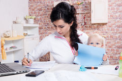 Femme avec le bébé travaillant de la maison Photos libres de droits