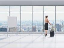 Femme avec le bagage dans le bureau Photo stock