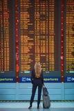 Femme avec le bagage de main dans le terminal d'aéroport international, regardant le conseil de l'information Photographie stock libre de droits