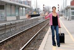 Femme avec le bagage ondulant à la station de train Image libre de droits