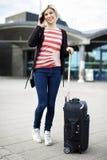 Femme avec le bagage parlant au téléphone portable en dehors de la stat de chemin de fer Image stock