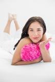 Femme avec le baiser de soufflement d'oreiller en forme de coeur dans le lit Image stock