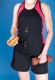 Femme avec le barbell et le hot-dog Photographie stock