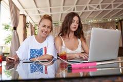 Femme avec le beau sourire posant tandis que son ami travaillant sur l'ordinateur portable pendant le petit déjeuner de matin en  Photos stock