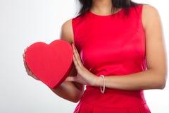 Femme avec le boîte-cadeau en forme de coeur rouge Photos stock