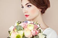 Femme avec le bouquet des fleurs dans des ses mains Photographie stock libre de droits