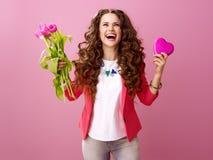 Femme avec le bouquet des tulipes et de la boîte en forme de coeur de chocolats Image stock