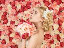 Femme avec le bouquet et fond complètement des roses image libre de droits