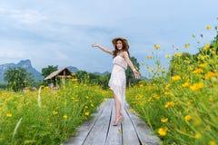 Femme avec le bras augmenté sur le pont en bois avec le gisement de fleur jaune de cosmos photographie stock libre de droits