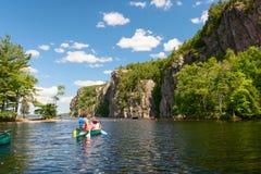 Femme avec le canoë-kayak d'enfant sur le lac Photographie stock