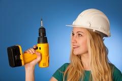 Femme avec le casque de constructeur et la clé électrique heureux de faire à Photographie stock libre de droits
