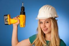 Femme avec le casque de constructeur et la clé électrique heureux de faire à Images libres de droits
