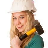Femme avec le casque de constructeur et marteau heureux d'effectuer le travail dur Photos stock