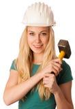 Femme avec le casque de constructeur et marteau heureux d'effectuer le travail dur Photo libre de droits
