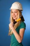 Femme avec le casque de constructeur et marteau heureux d'effectuer le travail dur Images stock