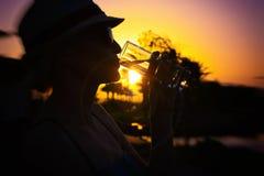 Femme avec le chapeau blanc et les lunettes de soleil roses avec la réflexion gentille des palmiers et du coucher du soleil buvan photos stock