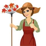 Femme avec le chapeau de jardin tenant le râteau illustration libre de droits