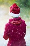 Femme avec le chapeau de Santa appréciant la première neige Photographie stock