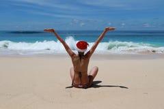 Femme avec le chapeau du ` s de Santa sur une plage tropicale Photographie stock libre de droits
