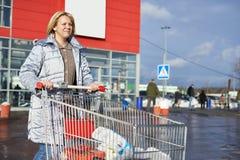 Femme avec le chariot sur se garer près du magasin Photos libres de droits