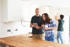 Femme avec le charpentier Looking At Plans pour la cuisine sur l'étiquette de Digital images libres de droits