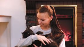 Femme avec le chat mignon se reposant près de la cheminée banque de vidéos