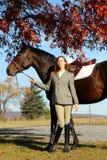 Femme avec le cheval de Brown dans l'automne Photographie stock libre de droits