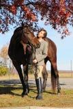 Femme avec le cheval de Brown dans l'automne Images stock