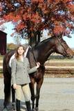 Femme avec le cheval de Brown dans l'automne Image stock