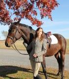 Femme avec le cheval de Brown dans l'automne Photo stock