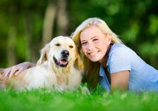 Femme avec le chien se trouvant sur l'herbe Image stock