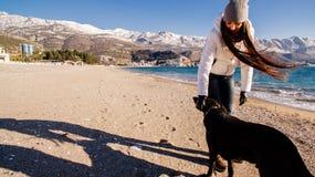 Femme avec le chien sur la plage en hiver Image stock
