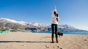 Femme avec le chien sur la plage en hiver Photographie stock libre de droits
