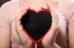 Femme avec le coeur en bois Photographie stock