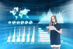 Femme avec le comprimé dans la chambre bleue avec des hologrammes Images libres de droits