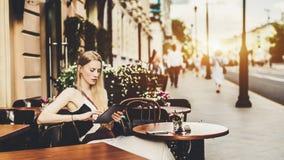 Femme avec le comprimé numérique en café de rue Photos stock
