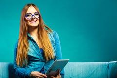 Femme avec le comprimé se reposant sur la couleur de bleu de divan Image stock