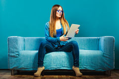 Femme avec le comprimé se reposant sur la couleur de bleu de divan Photographie stock