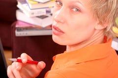 Femme avec le crayon lecteur à disposition et les livres photographie stock