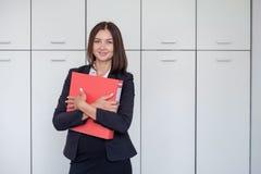 Femme avec le dossier rouge pour des documents sur le fond blanc Photographie stock libre de droits