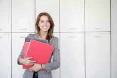 Femme avec le dossier rouge pour des documents sur le fond blanc Photos libres de droits