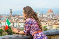 Femme avec le drapeau examinant la distance à Florence Image stock